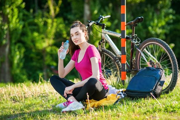 Brünette mädchen in sportbekleidung mit einem fahrrad ausruhen und trinkwasser