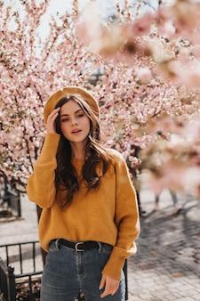 Brünette mädchen in stilvollem outfit und hut posiert in der nähe von sakura. porträt der frau im orangefarbenen pullover, in der jeans und in der baskenmütze, die im blühenden garten gehen