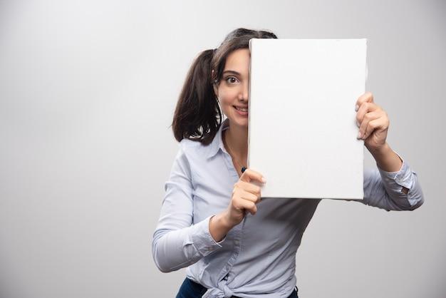 Brünette malerin versteckt ihr halbes gesicht hinter weißer leinwand.