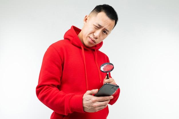 Brünette mann in einem roten pullover schaut auf das telefon durch eine lupe auf einem weißen
