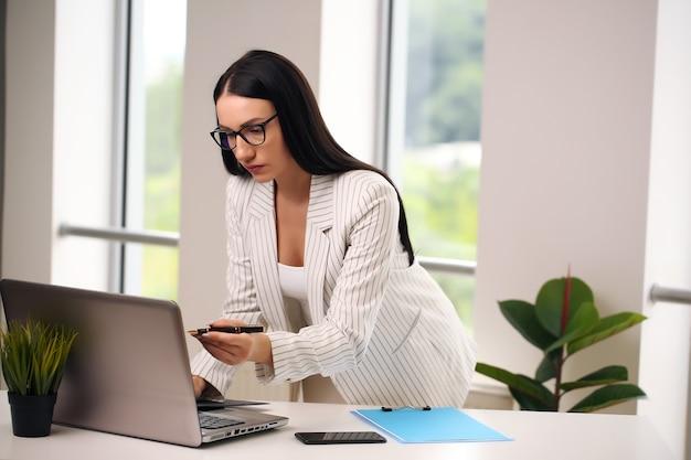 Brünette mit brille, manager mit stift, zeigt im laptop.