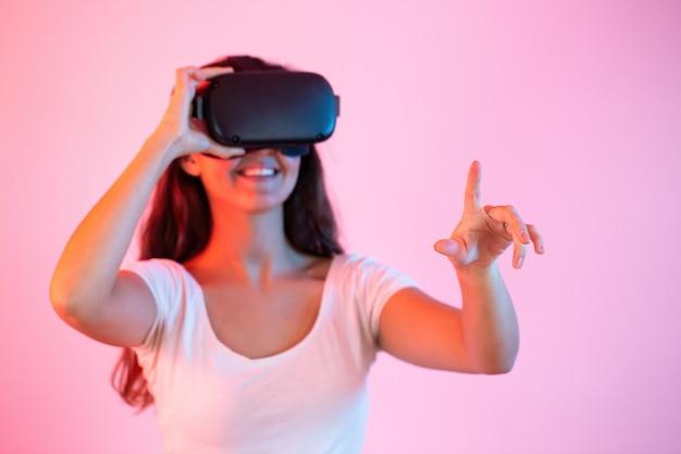 Brünette mit headset zeigt mit dem finger in die virtuelle realität