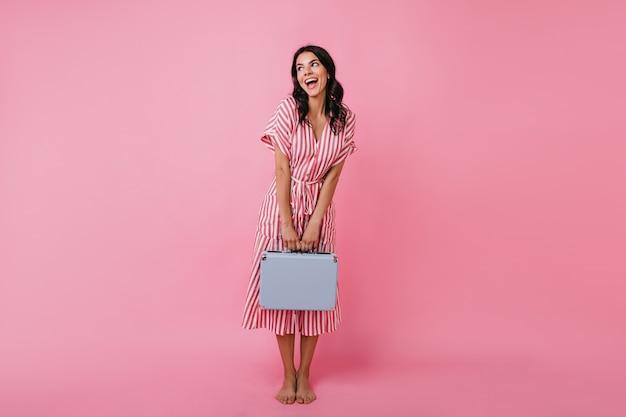 Brünette mit welligem haar posiert süß im gestreiften midikleid. frau im stilvollen outfit schaut interessiert weg.