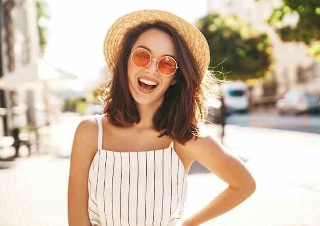 Brünette modell in sommerkleidung posiert auf der straße posiert