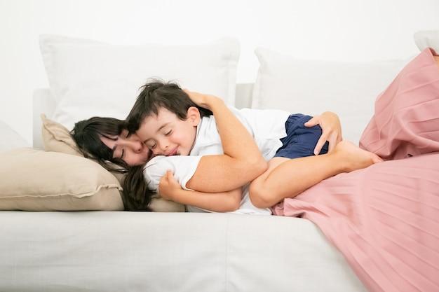 Brünette mutter, die auf der couch schläft und niedlichen sohn umarmt.