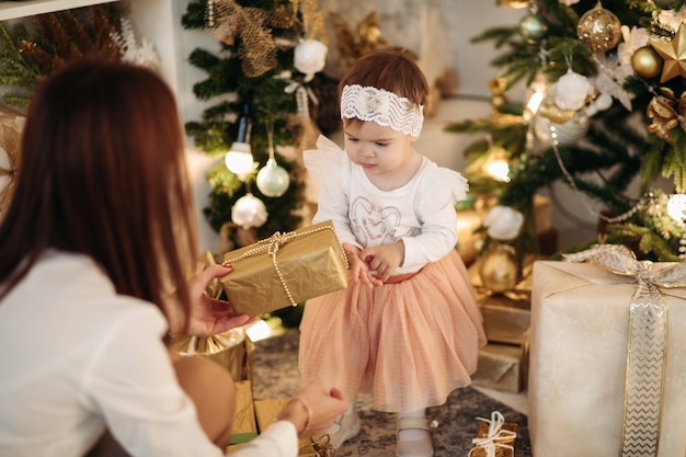 Brünette mutter, die entzückende kleine tochter im rosa rock, im weißen pullover und im stirnband weihnachtsgeschenk gibt
