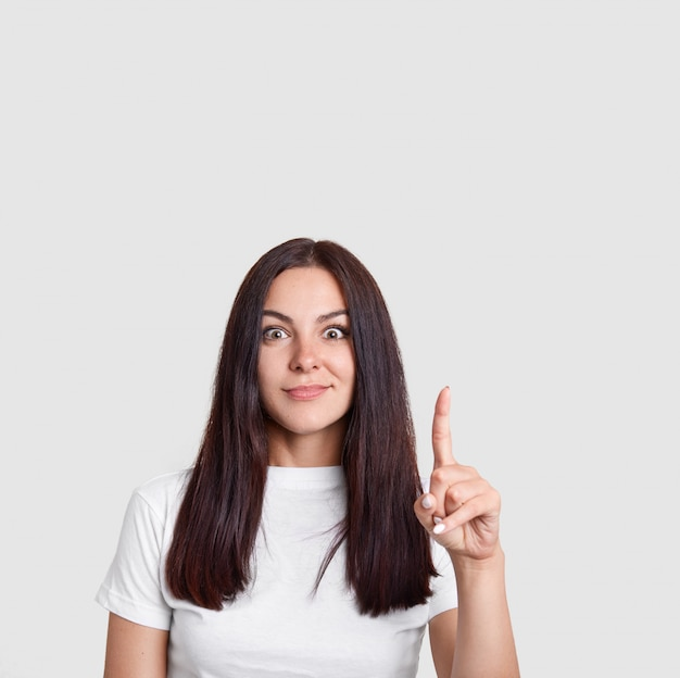 Brünette mysteriöse frau mit langen dunklen haaren, zeigt mit dem zeigefinger nach oben, hat ausdruck überrascht