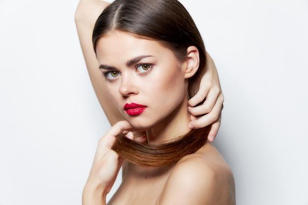 Brünette nackte schultern rote lippen saubere haut hält haare mit händen natürlich aussehen