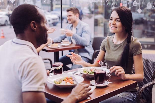 Brünette schöne frau, die an cfae sitzt, während sie lacht und salat genießt