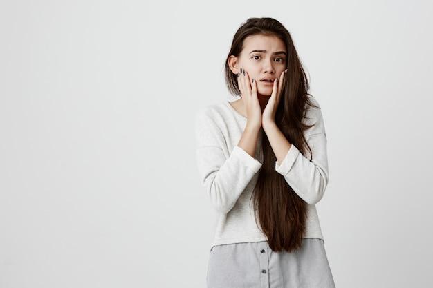 Brünette teenager-frau mit dunklen augen, die augenbrauen hochziehen, mit großen augen starren, hände auf ihren wangen halten und in panik besorgt sind, schlechte nachrichten zu hören. entsetzte junge frau mit schockiertem, verängstigtem blick