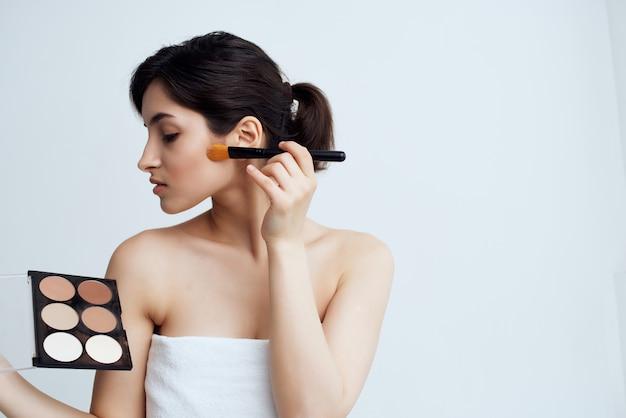 Brünette trägt pinsel make-up gesichtspflege hellen hintergrund