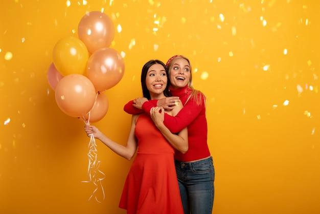 Brünette und blonde mädchen sind bereit für eine party mit luftballons