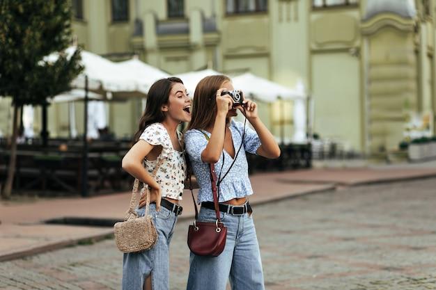 Brünette und blonde überraschte frauen in jeans und blumenblusen halten eine stilvolle handtasche und posieren draußen