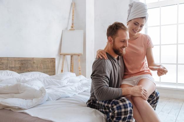 Brünette von überirdischer schönheit, die ihrem ehemann einen positiven schwangerschaftstest zeigt, während sie morgens auf seinem schoß sitzt