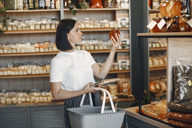 Brünette wählt essen. dame hält einen einkaufswagen. mädchen in einem weißen hemd im supermarkt.