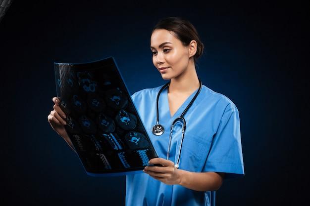 Brünetter arzt in der uniform, die röntgenbild betrachtet