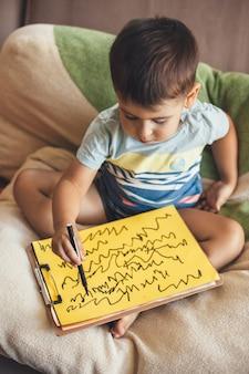 Brünetter junge, der auf einem gelben papier unter verwendung eines markers zeichnet, während er zu hause im bett sitzt