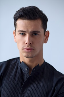 Brünetter junger mann im schwarzen t-shirt auf weiß