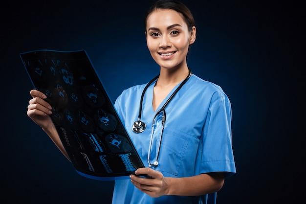 Brünetter lächelnder arzt in der uniform, die röntgenbild betrachtet