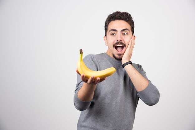 Brünetter mann, der banane glücklich betrachtet.
