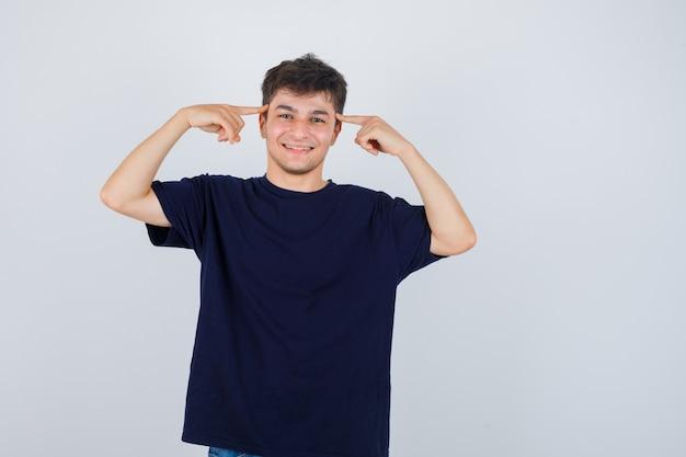 Brünetter mann, der finger auf schläfen im t-shirt hält und fröhlich, vorderansicht schaut.