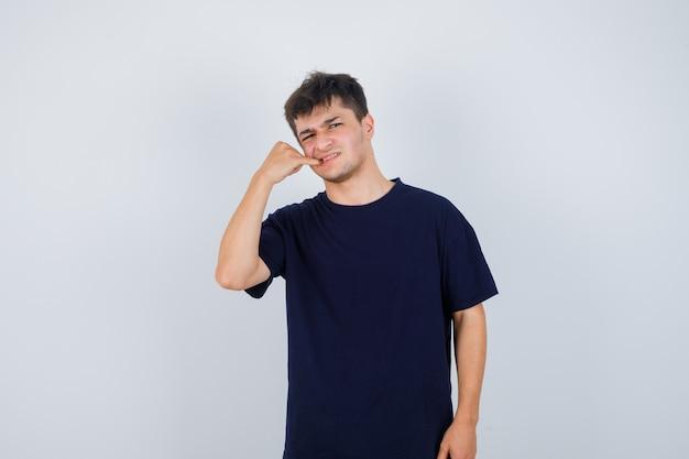 Brünetter mann, der finger im mund im dunklen t-shirt hält und unzufrieden schaut, vorderansicht.