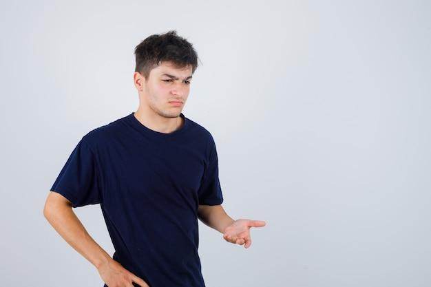 Brünetter mann, der fragende geste im dunklen t-shirt macht und verwirrt, vorderansicht schaut.