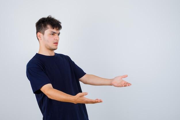 Brünetter mann, der fragende geste macht, seitlich in dunklem t-shirt stehend und verwirrt schaut.