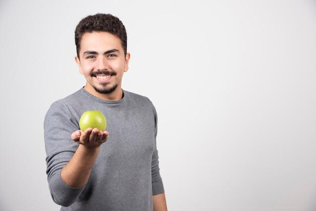 Brünetter mann, der grünen apfel glücklich hält.