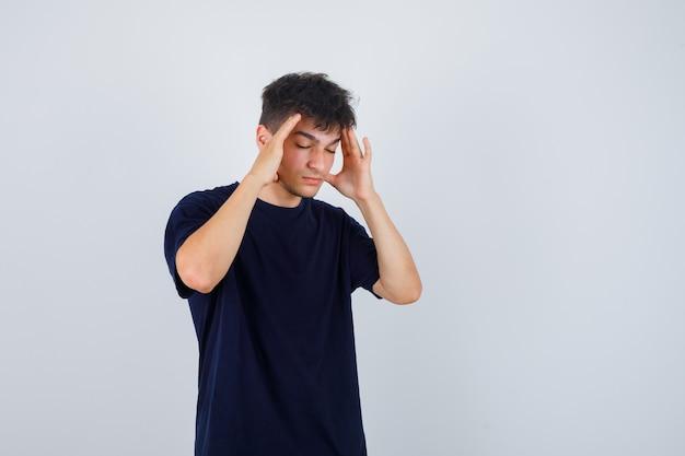 Brünetter mann, der hände auf kopf im dunklen t-shirt hält und nachdenklich aussieht.