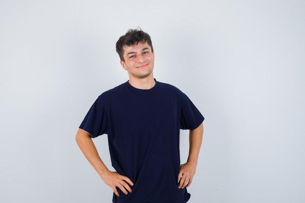 Brünetter mann, der hände auf taille im dunklen t-shirt hält und gut aussehend, vorderansicht schaut.