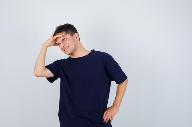 Brünetter mann, der hand über kopf im t-shirt hält und freudig schaut. vorderansicht.