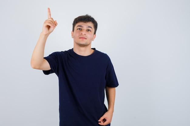 Brünetter mann, der im t-shirt oben zeigt und vorsichtig schaut, vorderansicht.