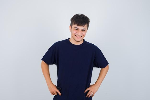 Brünetter mann, der kamera betrachtet, hält hände auf taille im dunklen t-shirt und schaut glücklich, vorderansicht.