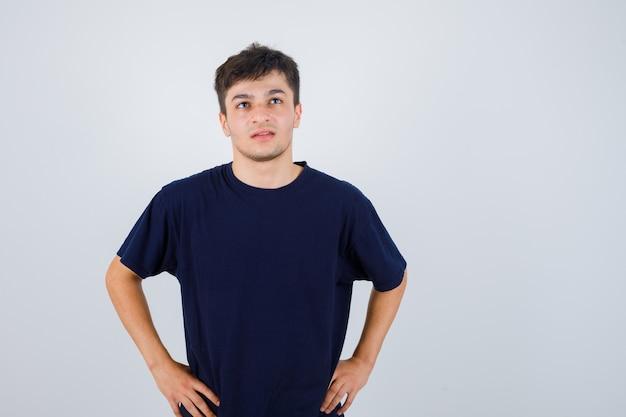Brünetter mann, der mit händen auf taille im t-shirt aufwirft und nachdenklich, vorderansicht schaut.
