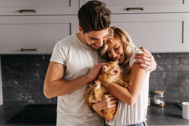 Brünetter mann, der seine katze betrachtet und frau umarmt. innenporträt der glücklichen familie, die mit haustier aufwirft.