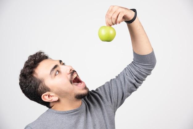 Brünetter mann, der versucht, grünen apfel zu essen.