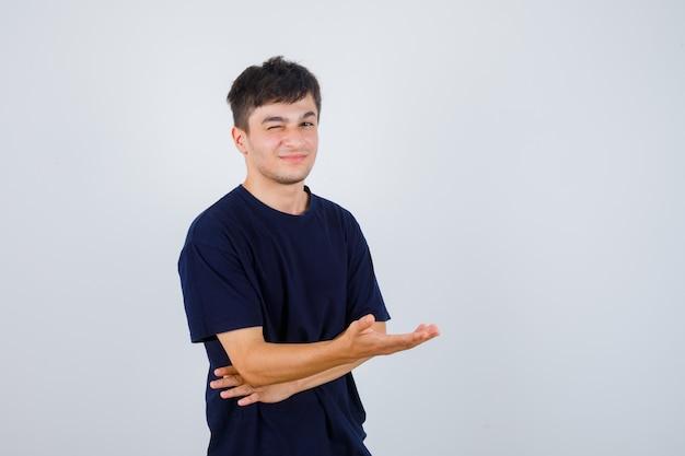 Brünetter mann, der vorgibt, etwas im t-shirt zu zeigen und fröhlich aussieht, vorderansicht.