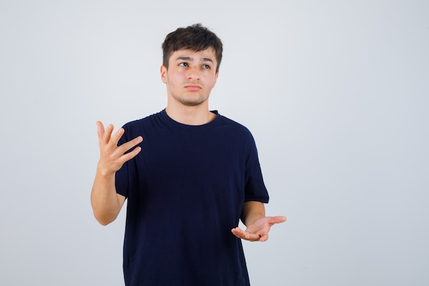 Brünetter mann, der vorgibt, etwas im t-shirt zu zeigen und nachdenklich aussieht. vorderansicht.