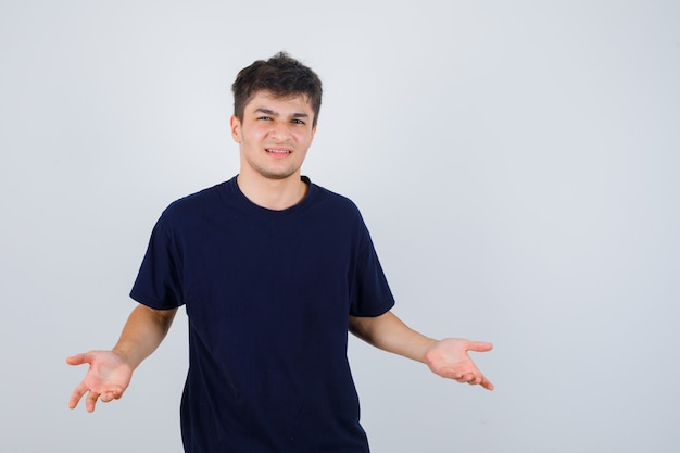 Brünetter mann im dunklen t-shirt, das das stellen der fragengeste macht und unzufrieden aussieht, vorderansicht.