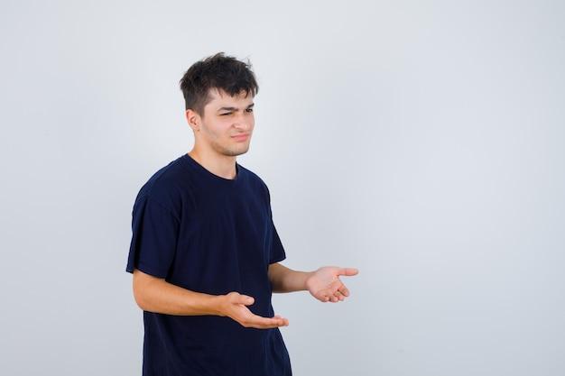 Brünetter mann im dunklen t-shirt, das fragen gestikulierend macht und unglücklich aussieht.