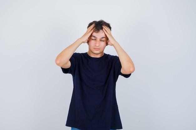 Brünetter mann im dunklen t-shirt, das hände auf kopf hält und müde, vorderansicht schaut.