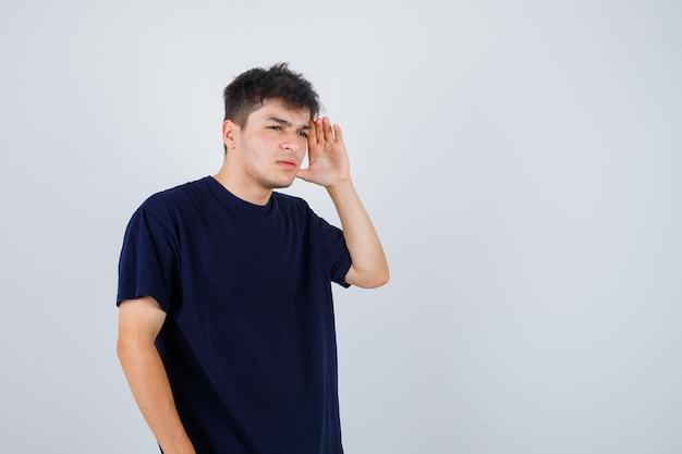 Brünetter mann im dunklen t-shirt, das hand hält, um klar zu sehen und unsicher auszusehen.
