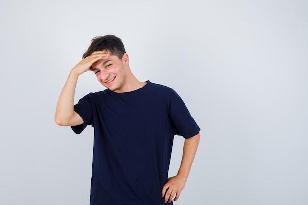 Brünetter mann im t-shirt, das hand über kopf hält und freudig, vorderansicht schaut.