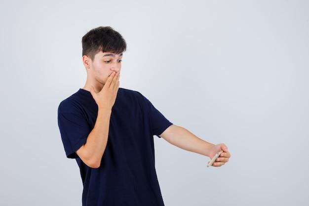 Brünetter mann im t-shirt, der handy betrachtet, während hand auf mund hält und ratlos, vorderansicht schaut.