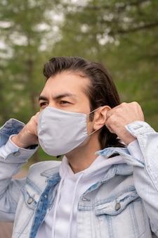 Brünetter mann in der jeansjacke, die draußen steht und stoffmaske auf gesicht setzt