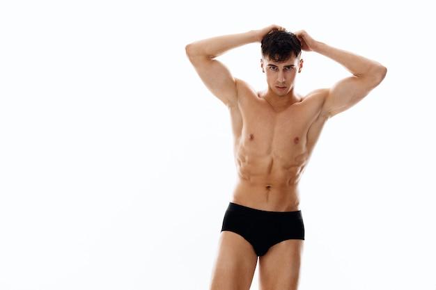 Brünetter mann in höschen und nacktem oberkörper hält hände in der nähe des gesichts