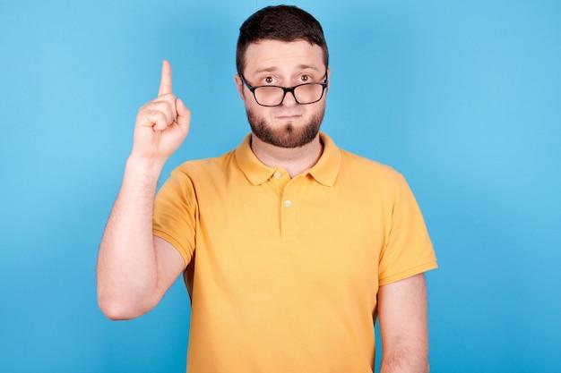 Brünetter mann mit brille zeigt daumen hoch, hat eine idee. auf blauem hintergrund isoliert.