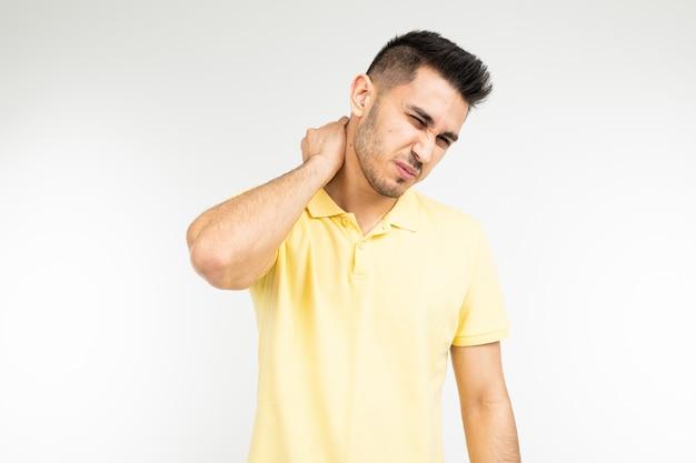 Brünetter mann spürt starke schmerzen im nacken in einem weißen studio