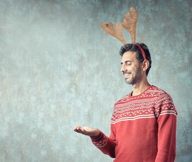Brünetter typ mit kurzem grauem bart, der in rotem weihnachtspullover und rentiergeweih-stirnband mit ausgestreckter hand mit offener handfläche nach oben lächelt